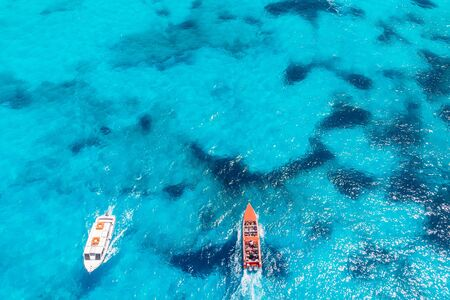 Pleasure Speedboat sailing on blue clear water of large coral reef with guided tour. Concept travel ship. Aerial view. Zdjęcie Seryjne