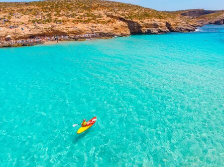 Kayak boat turquoise Blue Lagoon Comino Malta water sea, sunny day. Concept travel. Aerial top view