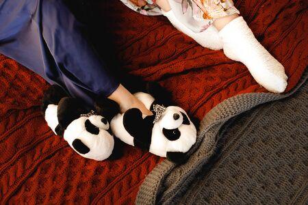 Female feet wearing cozy warm wool socks, panda Slippers close up