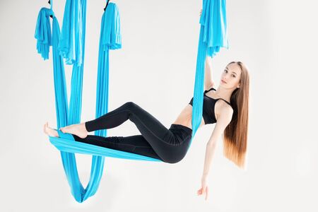 Young beautiful women practicing aerial yoga stretching in gym