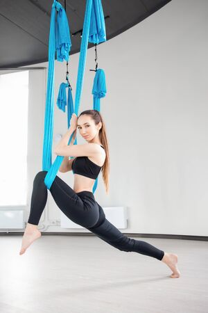 Aerial fly yoga in white gym, young gymnastics women in blue hammock Stockfoto