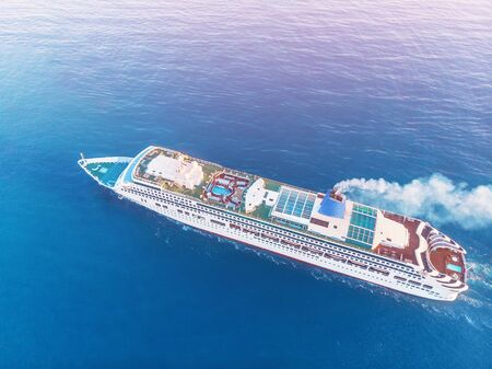 White Cruise ship in blue sea. Aerial top view