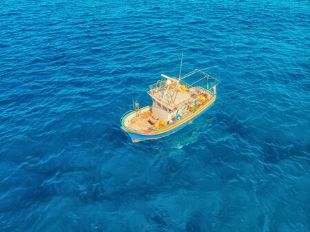 Fishing boat in blue sea water, fishermen set nets for fish. Aerial top view