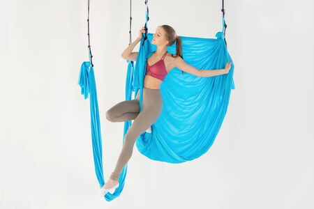 Beautiful young woman smiling at practicing aero fly yoga in white studio on blue hammocks. Concept stretching meditation Stockfoto