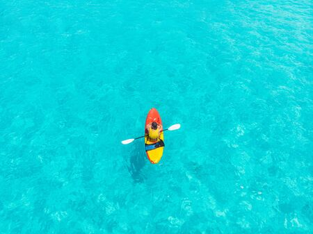 Kayak boat turquoise blue water sea. Aerial top view.