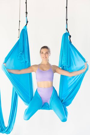 Beautiful young woman smiling at practicing aero fly yoga in white studio on blue hammocks. Concept stretching meditation,