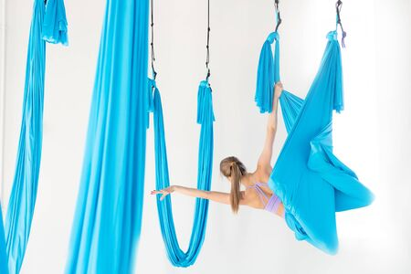 Young girl gymnast in sportswear doing stretching on blue hammock in white studio. Concept aero fly yoga