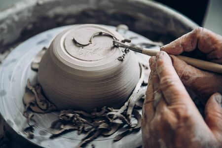 Turkish master paints and cuts clay plate patterns. Concept craft Stockfoto