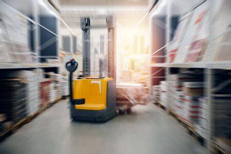Capannone industriale locale per stoccaggio materiali e legname, carrello elevatore. Concetto di logistica, trasporti. Effetto di sfocatura del movimento. Archivio Fotografico