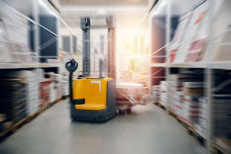 Warehouse industrial premises for storing materials and wood, forklift. Concept logistics, transport. Motion blur effect. Stock fotó
