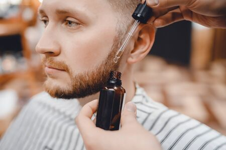Barber does oil for care and growth of beard, barbershop 版權商用圖片