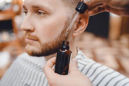 Barber fait de l'huile pour les soins et la croissance de la barbe, salon de coiffure Banque d'images
