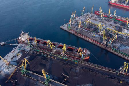 Loading coal mining in port on cargo tanker ship with crane bucket of train. Aerial top view