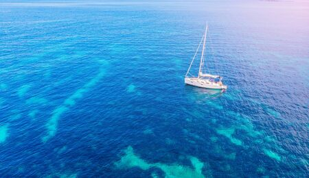 White yacht coral reef in Beautiful bay sea. Aerial top view