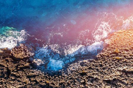El agua clara azur golpea la costa rocosa de la playa de coral. Vista aérea superior