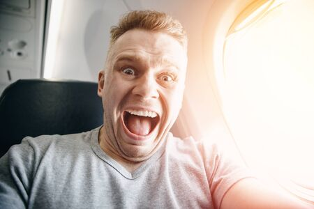 Passenger man in plane clutches his head, afraid of heights and flight. Scream and cry expression
