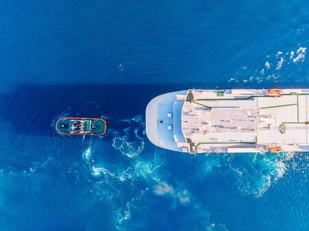 Tugboat towing large container ship blue sea port. Aerial top view