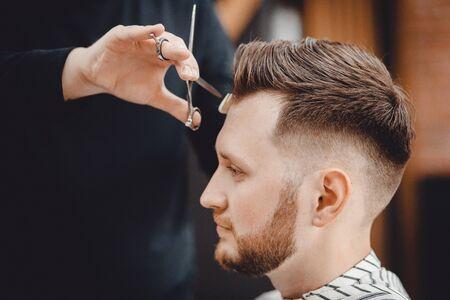 Barbershop, man barber in men hairdresser does hair with scissors