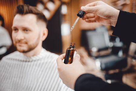 Oil for beard in dropper, process of moisturizing hair