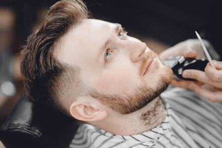 Barber shaves client beard in men barbershop with razor 写真素材