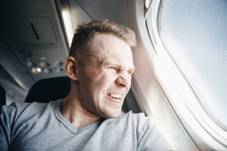 Man is angry in plane before departure. Concept aircraft delay