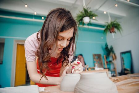 Work potter wheel. Happy young woman in red apron sculpts from clay