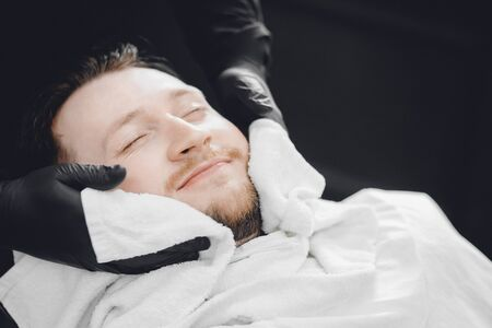 Barber steam face skin of man with hot towel before royal shave in Barbershop