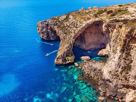 Blue Grotto in Malta. Pleasure boat with tourists runs. Natural arch window in the rock. Aerial top view.