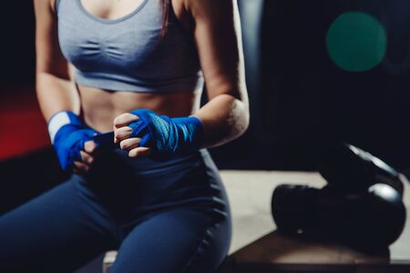 Young strong independent woman fists bandages for training in gym