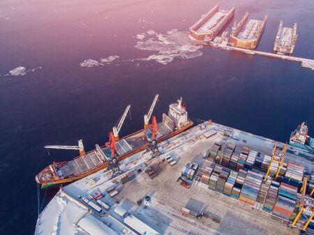 Containerfrachtschiff, das den Nordarktischen Hafen belädt. Konzept Güterverkehr Import Export und Geschäftslogistik, Luftbild Winter.