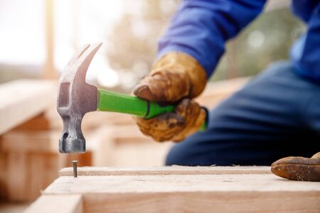 Male builder in yellow gloves hammer nail into wooden structure. Construction concept.