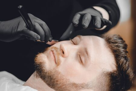 Barbershop. Hairdressers barber hair and beard with razor in salon