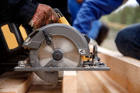 Builder uses portable circular saw tool to cut wood.