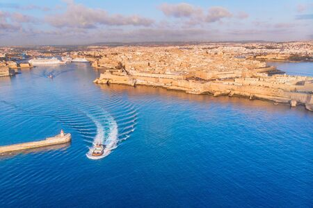 Tugboat sails to meet liner or cargo ship in port of Malta Valletta. Aerial view. Stock Photo