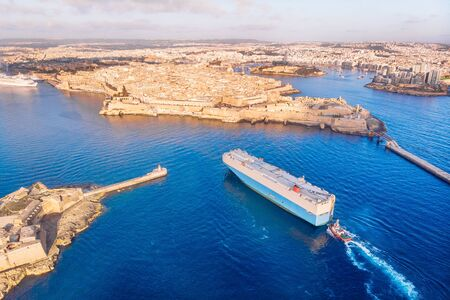 Tugboat towing large ship blue sea port Valetta, Malta. Aerial top view Stock Photo