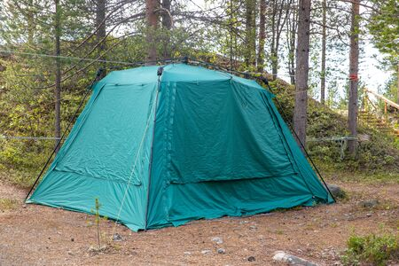 Tent for spending night and traveling green forest stands in Norway Banco de Imagens