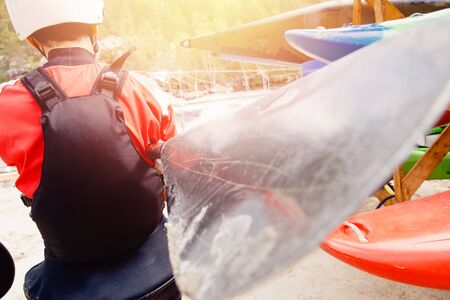Athlete man in rescue vest and helmet holds paddle prepares for rafting on kayak Stock Photo