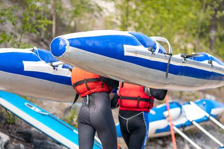 Athletes man carry kayak for rafting on water Stock Photo