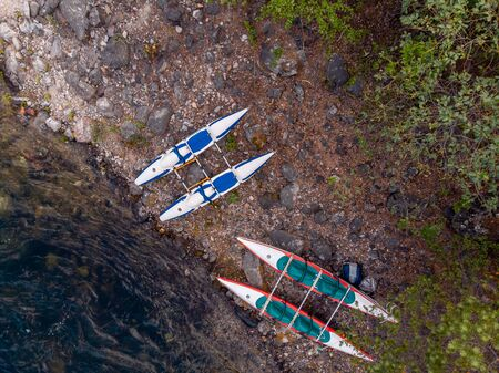 Rafting kayaks on bank of mountain river with rocky shore. Aerial top view