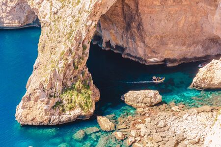 Gruta Azul en Malta. Embarcación de recreo con turistas corre. Ventana de arco natural en roca. Foto de archivo