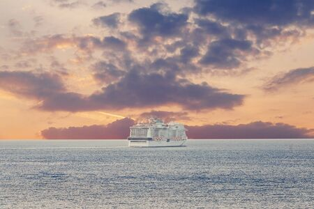Luxury cruise ship sunset in blue sea with clouds.
