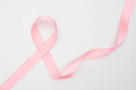 Curled pink ribbon with highlights isolated on white background, top view.
