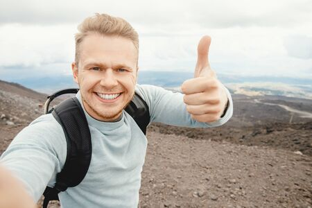 Etna volcano, Sicily Italy, man traveler with backpack makes selfie photo on background of mountains in ashes
