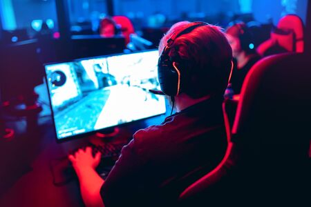 Professional gamer with headphones stream online games on computer pc in neon color blur background. Soft focus, back view.