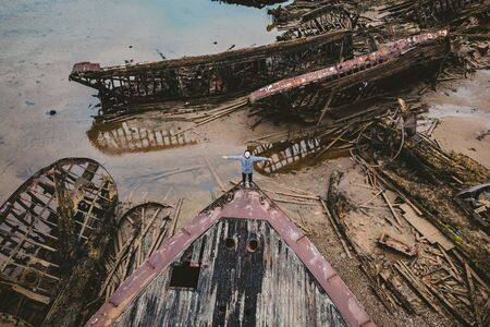 Tourist man looks at the cemetery of old wooden ships Teriberka, Murmansk region, Russia. Aerial top view Stock Photo