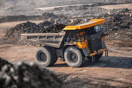 Duża żółta ciężarówka górnicza obciążona antracytem porusza się w kopalni węgla odkrywkowego.