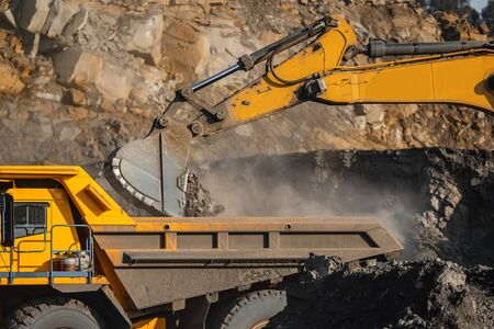 Open pit mine industry, excavator loading coal on big yellow mining truck for anthracite.