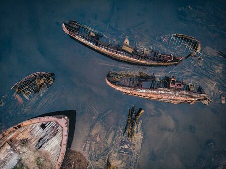 Cemetery of old ships Teriberka Murmansk Russia, wooden remains of industrial fishing boats in sea. Industrialization concept. Aerial top view Stock Photo
