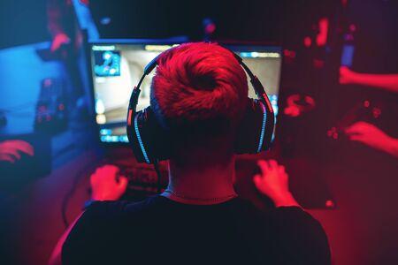 Professioneller Spieler, der Online-Spiele-Turniere PC-Computer mit Kopfhörern spielt, verschwommener roter und blauer Hintergrund