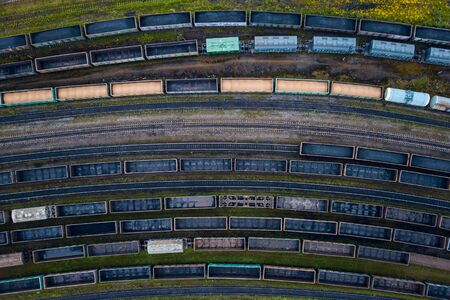 Freight cargo wagons train on bend of railway tracks, concept delivery. Aerial top view